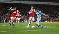 Leeds United's Jack Harrison with a shot under pressure from Arsenal's Sokratis Papastathopoulos and Mesut Ozil<br /> <br /> Photographer Rob Newell/CameraSport<br /> <br /> Emirates FA Cup Third Round - Arsenal v Leeds United - Monday 6th January 2020 - The Emirates Stadium - London<br />  <br /> World Copyright © 2020 CameraSport. All rights reserved. 43 Linden Ave. Countesthorpe. Leicester. England. LE8 5PG - Tel: +44 (0) 116 277 4147 - admin@camerasport.com - www.camerasport.com