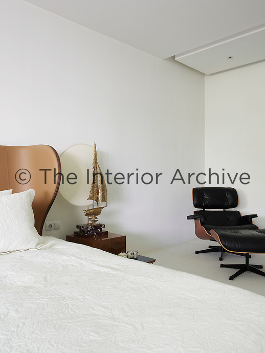 A corner of the simple bedroom is furnished with a Charles & Ray Eames leather lounge chair