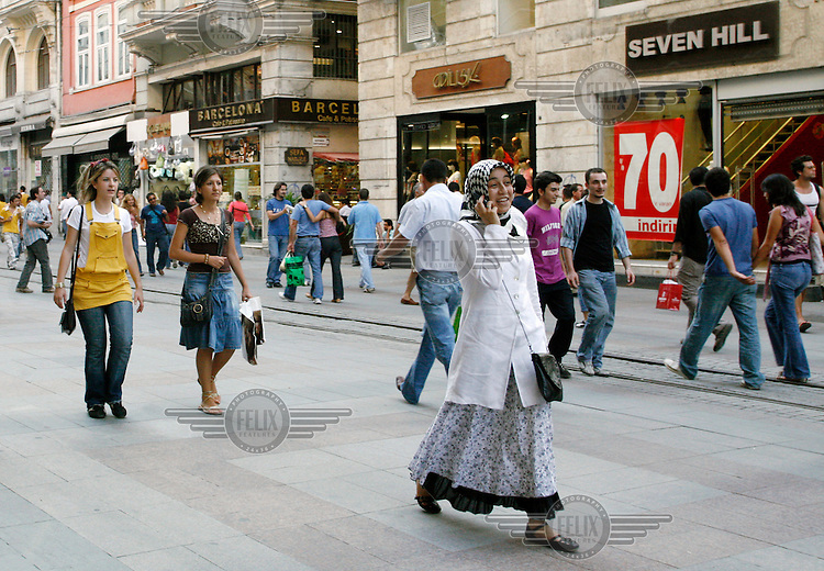 A veiled woman walks down Istiklal Avenue, a well-known shopping street in the historic Beyoglu district.