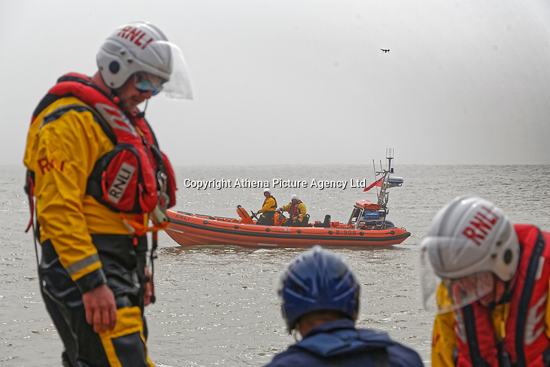 Pictured: A drone is seen in the distance near an RNLI rescuer who poses as a casualty on a slipway in on a beach St Donats, Wales, UK. Friday 20 April 2018 <br /> Re: The Royal National Lifeboat Institution (RNLI) and the Maritime and Coastguard Agency (MCA) have held a special media event to demonstrate how drones could be used in search and rescue activity in the future to help save lives at the Atlantic College in St Donats, south Wales, UK. <br /> The rescue scenario took place along a stretch of coastline in south Wales, featuring a drone, an RNLI lifeboat and an MCA helicopter winching the casualty to safety.