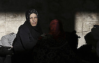 Pictured:A migrant woman rests in the passenger station Monday 22 February 2016<br /> Re: Thousands of migrants, most from Syria, have landed to the port of Pireaus, after crossing the border from Turkey to various islands like Lesvos and Kos in Greece.