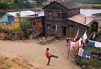 AJ2089, Chili, Chiloe Island, Boys playing soccer in front of his house with laundry hanging in the yard on Chiloe Island in Chile.