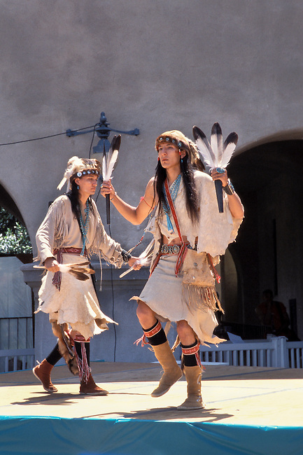 Two Navajo dancers dressed in traditional old style regalia made from deer hide dance with a pair of eagle feather dance wands