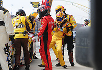 Oct. 11, 2009; Fontana, CA, USA; NASCAR Sprint Cup Series driver Kyle Busch (right) is pulled from his car due to flu like symptoms during the Pepsi 500 at Auto Club Speedway. David Gilliland (center) climbed in to replace Busch. Mandatory Credit: Mark J. Rebilas-