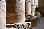 Man walking among Columns in Karnak Temple in Luxor, Egypt with hieroglyphics illuminated by the sun.