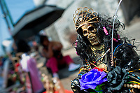 A figurine of Santa Muerte (Saint Death) is seen placed on the street during a religious pilgrimage in Tepito, a violent neighborhood of Mexico City, Mexico, 1 May 2011. The religious cult of Santa Muerte is a syncretic fusion of Aztec death worship rituals and Catholic beliefs. Born in lower-class neighborhoods of Mexico City, it has always been closely associated with crime. In the past decades, original Santa Muerte's followers (such as prostitutes, pickpockets and street drug traffickers) have merged with thousands of ordinary Mexican Catholics. The Saint Death veneration, offering a spiritual way out of hardship in the modern society, has rapidly expanded. Although the Catholic Church considers the Santa Muerte's followers as devil worshippers, on the first day of every month, crowds of believers in Saint Death fill the streets of Tepito. Holding skeletal figurines of Holy Death clothed in a long robe, they pray for power healing, protection and favors and make petitions to 'La Santísima Muerte', who reputedly can make life-saving miracles.