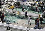 Crews onboard fishing boats readies their nets for the next day of fishing in the Strait of Tsugaru in the fishing port town of Omma, on the Northern most tip of Honshu, Japan. (Jim Bryant Photo)