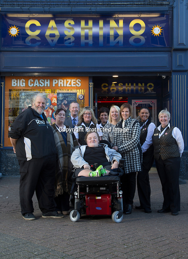 """20/11/15<br /> <br /> L/R: Alan Kent, Diane Kent, Simon Gudgeon, Lorna Cord, Helen Stockdale, Arron Kent, , Wanda Kidd, Linda Lindsay, Gemma Wylie and Janet Neal.<br /> <br /> Thanks to the joint fundraising efforts of customers and staff at Cashino adult gaming centre on Station Street Burton-On-Trent, Arron Kent, a seventeen year old teenager from Swadlincote has received a new, customised powered wheelchair to help boost his mobility. <br /> <br /> Arron, who lives with his mum, Diane, dad Alan and sister Tabitha, suffers from Osteogenesis Imperfecta – a severe brittle bone disease which has seriously affected Arron's ability to walk. His condition means his bones break easily, often from mild trauma or with no apparent cause.  <br /> <br /> Arron currently has a basic powered wheelchair  but as his condition progresses the chair is becoming inadequate to meet Arron's growing needs. <br /> <br /> Arron's mum Diane said: """"We are very grateful to Cashino and CHIPS charity for providing Arron with a new state of art powered wheelchair. As he develops into adulthood, it is important that he maintains his independence, this powered wheelchair with features including adjustable height, tilt in space and excellent manoeuvrability will literally revolutionise Arron's life. <br /> <br /> Diane continues """"Arron is developing his hobby of showing rabbits and the rise and fall feature of his new wheelchair means he can now reach the judging tables without needing the assistance of another person.""""<br /> <br /> Cashino, which operates 155 adult gaming centres across the country, is one of the main fundraisers for CHIPS, a charity set up on behalf of the casino and gaming industry, which aims to provide specialised wheelchairs for children and young people with severe mobility problems.<br /> <br /> Janet Neal, manager of Cashino Burton-On-Trent, presented Arron with his new wheelchair last Friday, 20th November 2015.<br /> <br /> Speaking after the presentation, Janet Neal sa"""