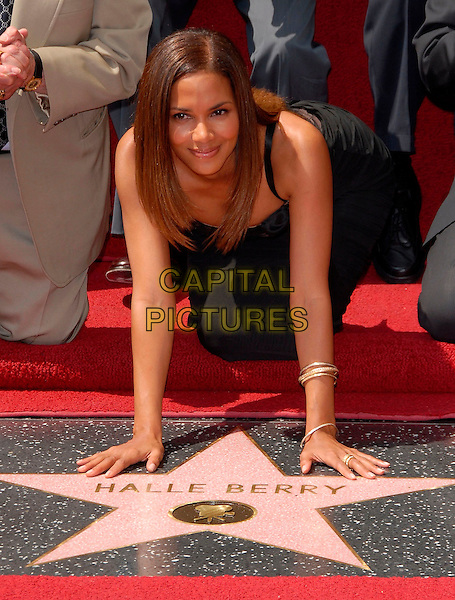 HALLE BERRY .Halle Berry is honored with a Star on The Hollywood Walk of Fame on Hollywood Blvd. infront of The Kodak Theatre in Hollywood, California, USA, on April 03rd 2007.half length hands leaning bending hands on star.CAP/DVS.©Debbie VanStory/Capital Pictures