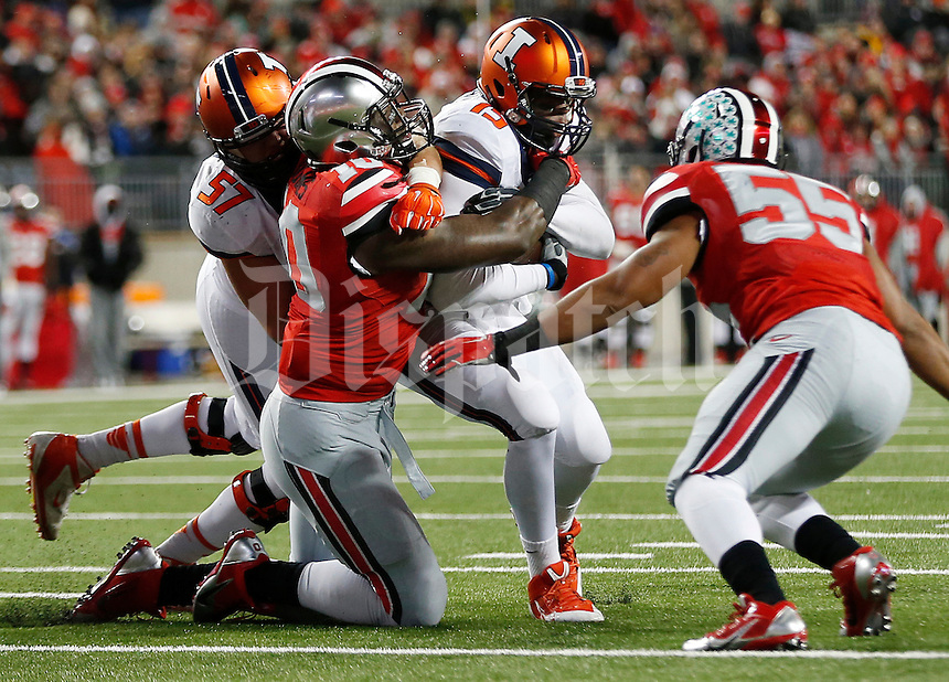 Ohio State Buckeyes defensive lineman Jalyn Holmes (10) and Ohio State Buckeyes linebacker Camren Williams (55) tackle Illinois Fighting Illini quarterback Aaron Bailey (15) during the college football game between the Ohio State Buckeyes and the Illinois Fighting Illini at Ohio Stadium in Columbus, Saturday night, November 1, 2014. The Ohio State Buckeyes defeated the Illinois Fighting Illini 55 - 14. (The Columbus Dispatch / Eamon Queeney)