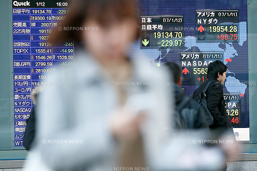 Pedestrians walk past an electronic board showing Japan's Nikkei Stock Average, which dropped -229.97 or -1.19%  on January 12, 2016. The Nikkei Index fell to 19,134.70 after uncertainty arising from President-elect Donald Trump's news conference. (Photo by Rodrigo Reyes Marin/AFLO)