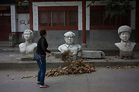 Huanggang, Hebei province, China - A worker sweeps fallen leaves in front of a bust of the late chairman Mao Zedong (Centre), October 2014.
