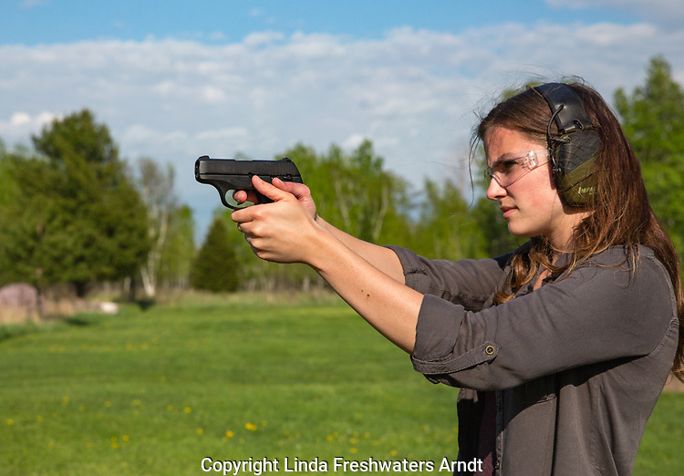 Young woman shooting a Ruger LC9s pistol