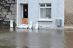 A resident looks out their front door at the high tide at Ship Street. Photo:Colin Bell/pressphotos.ie