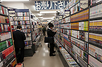 Salarymen or Japanese male office workers look at secondhand books in a Book off Store in Meguro, Tokyo Japan. Friday November 28th 2014