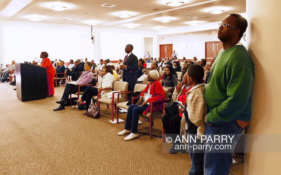 MAY 9, 2011 - MINEOLA, NY: Regis Lawrence Thompson of Hempstead at podium during Nassau County Legislative Redistricting public hearing, and, at center, standing in audience Dennis Jones, second vice president of the New Hempstead Democratic Club, and (at right in green sweater) Ramel Smith of Hempstead standing with his son Ramel Smith Jr. Ms. Thompson refuses to leave when told to do so by (not seen here) Nassau County Presiding Officer Peter Schmitt. At Nassau County Executive and Legislative Building at 1550 Franklin Avenue, Mineola, New York, USA on May 9, 2011.