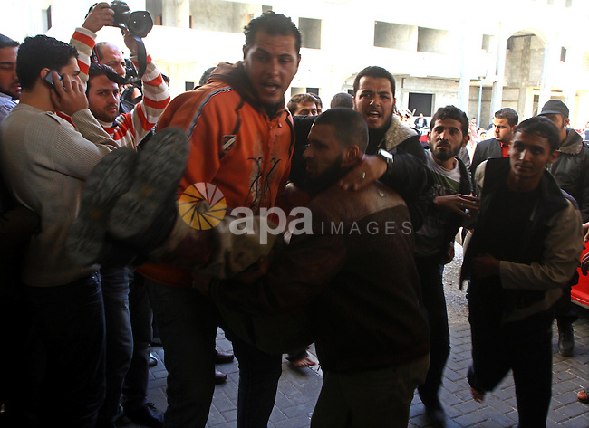 Palestinians carry a wounded man into al-Shefa hospital in Gaza City on Feb. 23, 2011. Eleven Palestinians were wounded Wednesday by Israeli artillery shelling in Gaza City, witnesses and medical sources said. Photo by Ashraf Amra