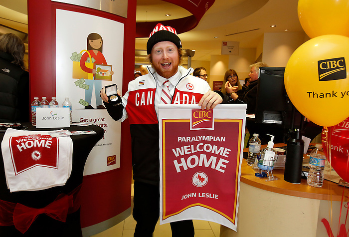 Ottawa, ON - March 28 2014 - John Leslie of the para-snowboard team displays his limited edition gold-plated coin and personalized Welcome Home banner at the CIBC Paralympic Welcome Home Event at CIBC South Keys Banking Centre in Ottawa (Photo: Patrick Doyle/CIBC)