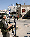 Israeli border police officers stand guard outside a building occupied by Jewish settlers in the West Bank city of Hebron April 3, 2012. Israeli Prime Minister Benjamin Netanyahu overruled the planned eviction on Tuesday of Jewish settlers from the building in Hebron that is a flashpoint of tensions with Palestinians.  Photo by Mamoun Wazwaz