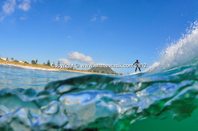 Warm water and sunny conditions make the 4ft swell superb conditions for surfers in this paradise! Mount Maunganui in the distance stands guard over the Tauranga Harbour and at this angle the impression is the surfer is about to ride uphill!