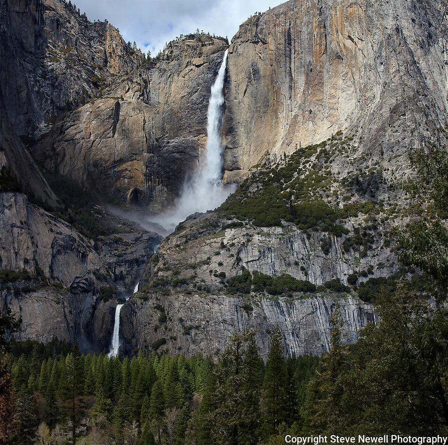 """Yosemite Falls Waterfall"" Yosemite National Park, California. I spent two weeks in the Spring of 2013 climbing up the opposite canyon's wall in order to get an angle that captured all three sections of the waterfall.  I learned on the Yosemite National Park's website that no one had a photograph of the middle section of the waterfall.  Their description of the middle section is ""often ignored middle section""  All other photographers only have photographs showing an angle that has the upper and lower sections in view.  In this photograph you can just start to see the water falling in all three sections. I had to climb down and return moving further up the canyon to get an angle to see directly into the middle section.  During sunset the color of all of Yosemite's rock formations change drastically."
