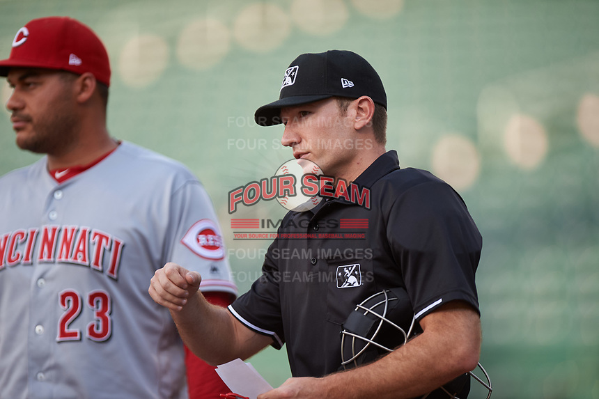 Home plate umpire Michael Corbett meets with AZL Reds bench coach Donald Lutz (23) during the lineup exchange before an Arizona League game against the AZL Cubs 2 on July 23, 2019 at Sloan Park in Mesa, Arizona. AZL Cubs 2 defeated the AZL Reds 5-3. (Zachary Lucy/Four Seam Images)