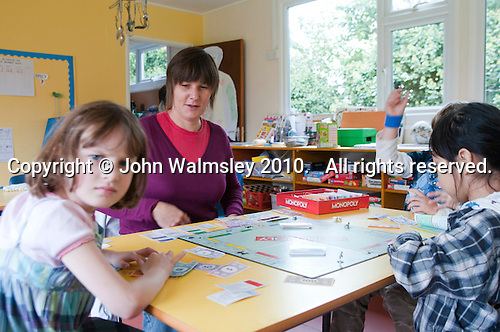 Carmel Linton, playing Monopoly with the youngest kids, Summerhill School, Leiston, Suffolk. The school was founded by A.S.Neill in 1921 and is run on democratic lines with each person, adult or child, having an equal say.  You don't have to go to lessons if you don't want to but could play all day.  It gets above average GCSE exam results.