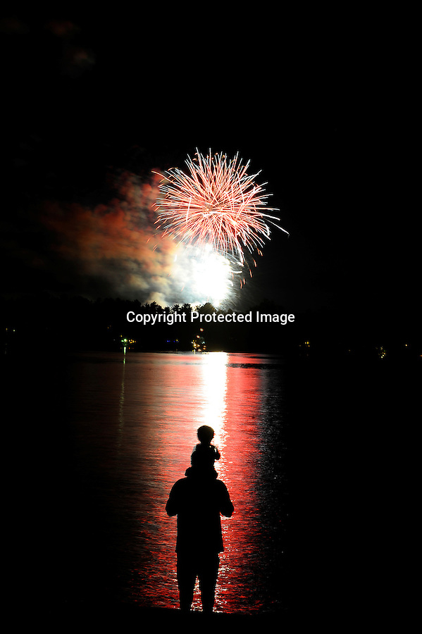 A father and young son watch fireworks over Lake Minocqua, WI.