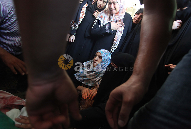 Palestinian relatives mourn on the bodies of members of the Alouh family, killed in an Israeli airstrike during their funeral in Deir al-Balah in the center of the Gaza Strip, on August 20, 2014. An Israeli air strike on a house in the Gaza Strip town of Deir el-Balah killed a pregnant woman, three young children and two male relatives, emergency services said. They named the dead as Rafat Aloah, 32, three of his children, his brother Mohammed 21 and the woman, Nabilah Aloah, whose relationship to the others was not immediately clear. Photo by Ashraf Amra