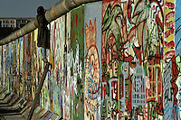 A curious tourist uses a ladder to peep over the top of the Berlin Wall