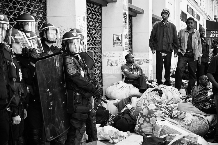 Just expulsed by the CGT security service after 14 months of occupation, workers watch the riot police securing the building's doors to prevent people from entering back. Mattresses, blankets, dishes and personal belongings were removed from inside and piled on the sidewalk, but many people lost some properties.