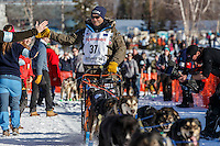 Robert Sorlie gives a high-five as he leaves the start line during the Restart of the 2016 Iditarod in Willow, Alaska.  March 06, 2016