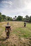 INDONESIA, Flores, men walk through the center of a village called Kampung Tutubhada in Rendu