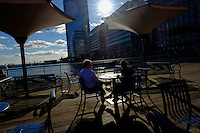 People enjoy lunch on a boardwalk during a sunny day in the Neighborhood of Exchange Place in New Jersey, 12/15/2015 Photo by VIEWpress