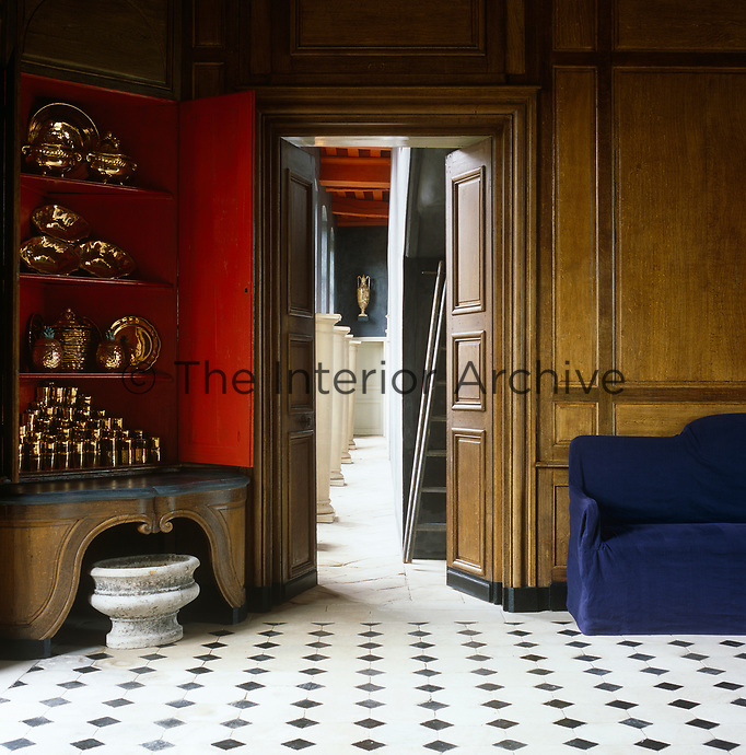The panelled walls of the chateau's entrance hall have been painted a wood-grained tromp l'oeil with a corner cabinet displaying a Chinese red interior