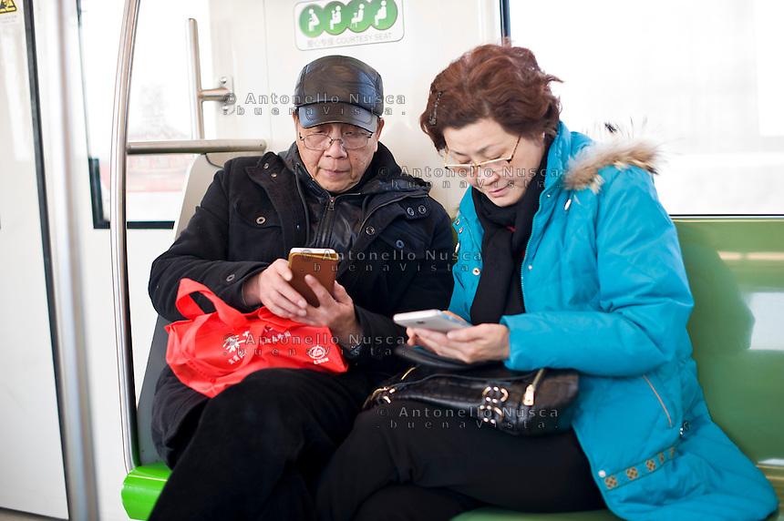 Una coppia di anziani chattano con i loro telefoni in un treno.<br /> A chinese couple chatting on their mobile phones