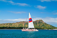 A catamaran with a red and blue striped sail glides on blue water with Diamond Head in the background.