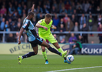 Jake Carroll of Hartlepool United hits the ball under pressure from Janoi Donacien of Wycombe Wanderers during the Sky Bet League 2 match between Wycombe Wanderers and Hartlepool United at Adams Park, High Wycombe, England on 5 September 2015. Photo by Andy Rowland.