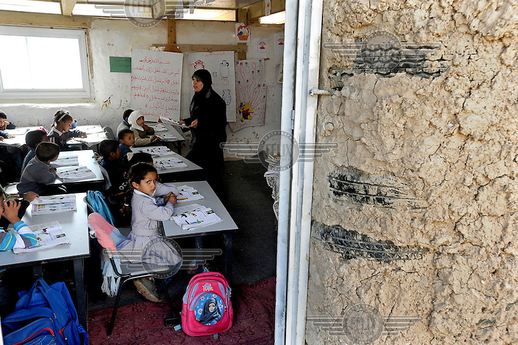 Bedouin school children sit in a classroom listening to their teacher in the unrecognised encampment of the Jahalin tribe along the Jerusalem - Jericho road in a part of the West Bank under Israeli control. The building is made out of mud and tyres.