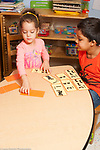 Education preschool 4 year olds boy and girl playing memory game, matchimg cards with number counting concepts