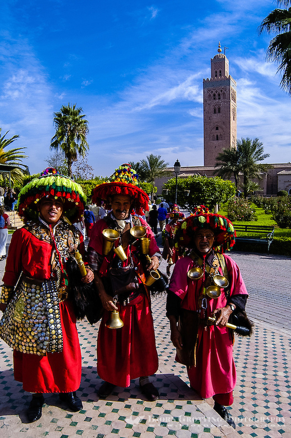 Morocco, Marrakesh. Colourful water salesmen in front of the The Koutoubia Mosque. They will charge for a photo.