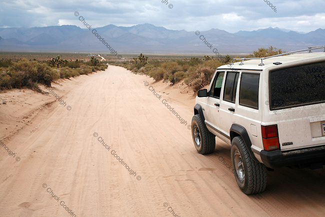 This Stock Photo shows a Jeep Cherokee 4x4 vehicle on deep sand road heading towards the Southern Sierra Mountains in California's South Western Mojave Desert. Harts Road.