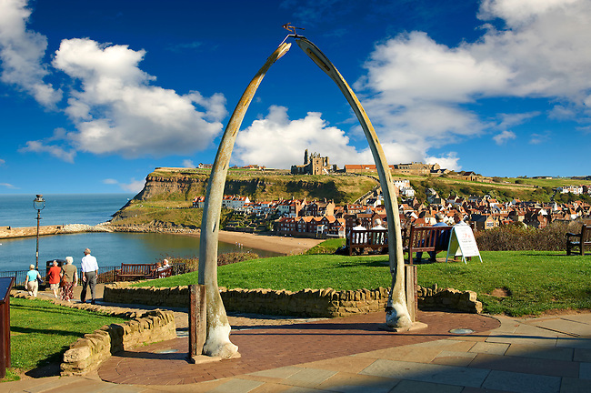 Whale Bone arch overlooking Whitby harbour with Whitby Abbey on the headland . Whitby, North Yorkshire, England