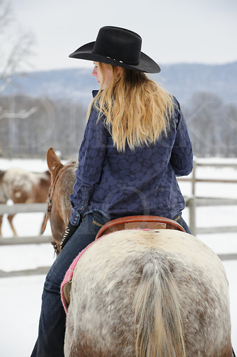 Pretty blonde woman riding her Appaloosa horse, twenty-something in casual western wear with black cowboy hat, rear view looking left, winter outdoors in snow, Pennsylvania, PA, USA.