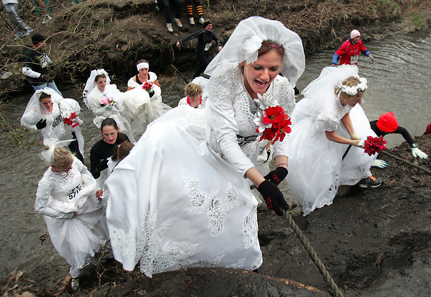 Heather Shives, 21, of Knoxville, leads her team, The Runaway Brides, out of a creek while running in the 30th Living History Farms Off-Road Race on Saturday.