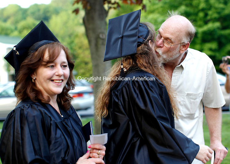 Winsted, CT- 26, May 2011-052611CM15  Jessica Banholzer (right) of Winsted, kisses her dad, Craig, as her mother Mary, walks beside her during Northwest Community College at East End Park in Winsted Thursday night. Jessica and Mary both received their diplomas from NCCC. Christopher Massa Republican-American