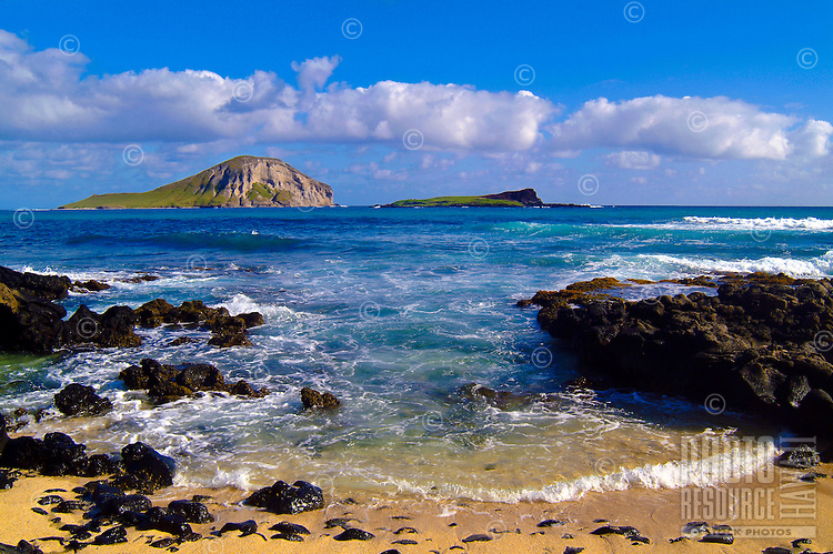 Gentle surf rolling past aa ( a'a ) lava rocks onto the beach at Makapuu, near Sea Life Park, part of a scenic drive on Oahu. Rabbit Island ( Manana ) in the background
