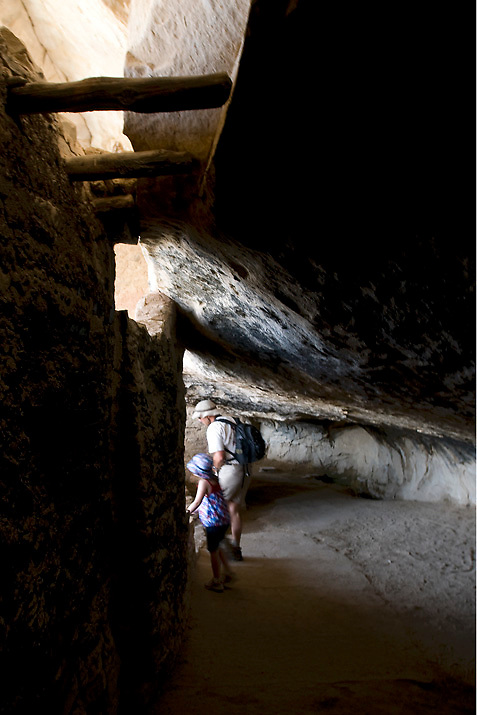 A father and daughter explore the dark alcove behind Balcony House Ruin in Mesa Verde National Park, CO