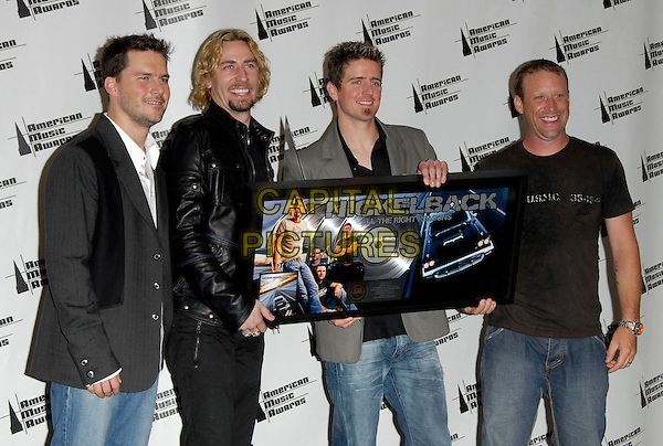 NICKELBACK.The 34th Annual American Music Awards held at The Shrine Auditorium in Los Angeles, California, USA. - Pressroom..November 21st, 2006.half length black suit jacket hand gesture award trophy grey gray leather plaque.CAP/DVS.©Debbie Van Story/Capital Pictures
