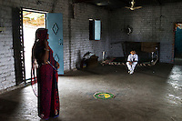 Fairtrade cotton farmer Sugna Jat, 30, goes about her household chores in the morning at home in Maheshwar, Khargone, Madhya Pradesh, India on 13 November 2014. Her son, Hemant (in white, aged 6), is a student in the Vasudha Vidya Vihar school that was built using the Fairtrade Premium, where Fairtrade farmers get a 5% discount on the fees. Photo by Suzanne Lee for Fairtrade
